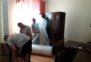 Мастера приступают к упаковке шкафа для переезда
